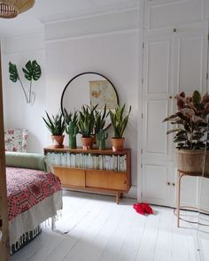 Boho bedroom - white floors, round mirror, vintage sideboard and mother in law's tongue plants.