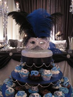 Wedding cake for a Venetian masquerade theme. Top mask made out of gumpaste. Top tier is vanilla with fondant accents. Little gumpaste masks on the cupcakes. Decorated the cake stand and 200 cupcakes = really time consuming! Thx for looking.