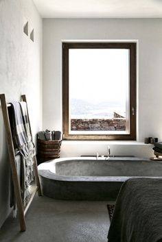 Tub with large window to enjoy the Syros city and ocean view, wooden ladder as towel hanger, and wooden basket