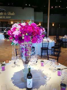 hot pink and purple tall centerpiece featuring dahlias, rose, carnations and naked ladies