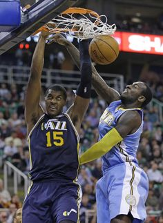 Utah Jazz's Derrick Favors (15) dunks the ball on Denver Nuggets' J.J. Hickson (7) in the fourth quarter during an NBA basketball game Monday, Nov. 11, 2013, in Salt Lake City. The Denver Nuggets won 100-81. (AP Photo/Rick Bowmer)