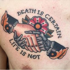 """This particular design features the proverb, """"Death is Certain, Life is Not,"""" and includes the image of a normal hand shaking a skeletal hand. It also features a red flower at its center, and despite its message, doesn't have any macabre images."""
