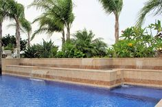 A luxurious custom water feature design by Ocean Quest Pools using Authentic Durango Veracruz pool coping.