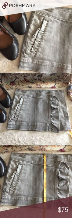 """NWOT 7fam Miniskirt 💥 MADE IN THE USA 🇺🇸 7 For All Mankind skirt. Exquisite!!! Grey denim mini features a wrap style closure with single interior and exterior buttons. Slightly asymmetrical front hem with ruffled vertical edge. Single zippered front pocket and 2 back patch pockets. 15"""" across waist laid flat. 12"""" long. Unique, edgy with feminine details, sexy. This skirt is all of that... NWOT, never worn 7 For All Mankind Skirts Mini"""