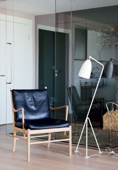 Modern living room featuring the Grasshopper Floor Lamp from Gubi and the Colonial Chair OW 149 from Carl Hansen & Son.
