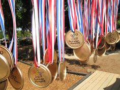 Home made Gold Medals for Preschool Summer Olympics!  Used the tops of those frozen juice cans along with red/white/blue ribbon & gold spray paint