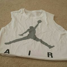 """Cropped Jordan Shirt! • Description/Information - Cut White Cropped Shirt With Grey Jordan Symbol And Black """"Air"""" Lettering  • Condition - Great  • How It Fits - True To Size  • Flaws - None  • Thanks For Checking Out My Listing !  • Let Me Know If You Have Any Questions ! • If You Ask For Lower Price I Will Not Respond.  Just Use Offer Button And We Can Make A Deal :)  • This Comes From A Smoke Free Home ! Tops"""
