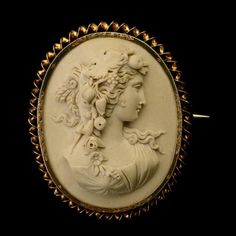 Sold For $600 in Jan. 2013  VICTORIAN CARVED LAVA CAMEO, 14K YELLOW GOLD BROOCH. Featuring an ornate profile of a goddess with a garland of fruit and flowers in her hair, bezel set in a 14k yellow gold mounting measuring approximately 56 x 46 mm with a finely engraved bezel and a twisted wire border, completed with a pin stem and catch. 17.1 dwts.