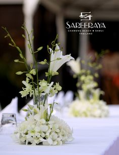 Long table centerpiece with white orchids and lilies.