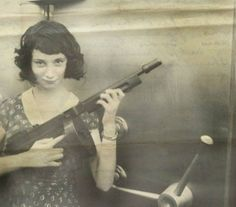 Gangster Madam Moll holding her M1928 Thompson in front of a bank safe she just robbed 1927