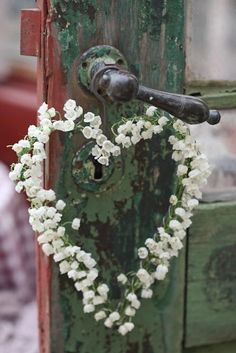 weathered green door with dainty heart wreath