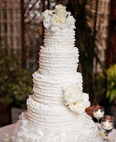 White wedding cake with white ruffles and flowers