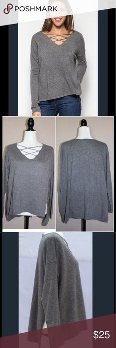 Cross My Heart Sweater Heather Grey  Hi-lo hem with high rise side slits  Criss Cross detail in front  65% Cotton, 35% Acrylic  Small - 4/6, Medium - 8/10, Large 12/14  Editor's Note: This garment runs large and is intended to fit loosely. For a tighter fit, size down. Sweaters V-Necks