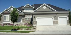 Gray Stucco with rock accent and white trim. Goes well with the dark roof.