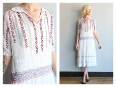 Gorgeous and rare 1920s Bohemian embroidered dress. Smocked waist, embroidered detail throughout. White with red and blue embroidered. Drop