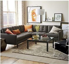 Photo illustrates Crate and Barrel's Orissa rug layered on top of a jute rug with a Petrie sectional sofa in color graphite.