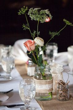 Rustic, whimsical centerpieces featuring roses, tall greenery and jars wrapped in burlap and lace. {Sara Johnson Photography}