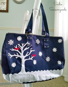 Thrift store makeover: DIY winter snow scene on a blue canvas tote bag using felt, eyelet lace trim, and vintage crocheted doilies by Sadie Seasongoods / www.sadieseasongoods.com