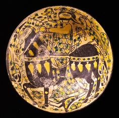 Earthenware bowl, covered with a white slip and painted in black, yellow, and green under a transparent glaze  Eastern Iran, Nishapur; 10th century  H: 8.5; Diam: 22 cm  This colorful bowl belongs to a special group of ceramics that was produced at the same time as slip-painted types that were far simpler with regard to both color and motif. A horseman in chain mail lifting a sphere high in his right hand is riding off with something that could be viewed as a gigantic hunting falcon.