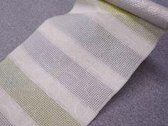 【となみ帯+汕頭刺繍③】 この帯は総紗縫。 シンプルな横段柄に合わせて刺繍も横段に施しています。  刺繍する時間を早くするためには、多くの職人が一つの帯に関わり、分担すると可能かもしれません。しかし、となみ織物では一人の職人が最初から最後まで、一本の帯に責任を持ち刺繍を施します。  そのため、帯の中に刺繍の大きさ、ムラが生じ難くなり、全体で見ると刺繍目が揃った美しさに繋がります。