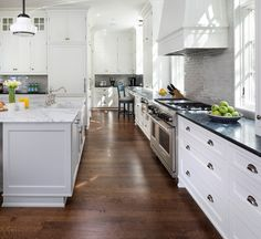 White Kitchen with pale gray island. Classic white kitchen cabinets with gray kitchen island. #WhiteKitchen #gray #island John Kraemer & Sons.