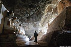A man walks past Buddha images inside Ya The Byan cave