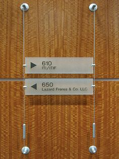 Cable/Rod Suspended Office Directories – designed and fabricated to your individual requirements. Select from wall-mounted, projecting or cable/rod suspended. Choice of using glass, acrylic, or other materials: frosted, colored, textured, metal finishes or wooden finishes, high-performance vinyl applications, digital prints, etc.