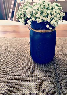 Baby's breath in a distressed mason jar on top of a burlap runner.