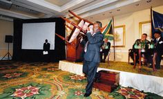 Ex President Thabo Mbeki holds his chair aloft and passing it on to a woman in the audience as there were no more seats left for her to sit on