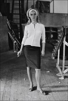 Brigitte Bardo wears an adorable pencil skirt with a wide headband, and a cardigan sweater.