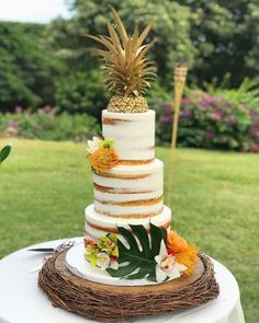 Tropical Semi Naked wedding cake and Gold Pineapple cake topper. Tropical leaves and flowers as detail. Rustic wood cake stand. A lovely choice for an outdoor wedding or beach wedding. | wedding cake ideas | #weddinginspiration