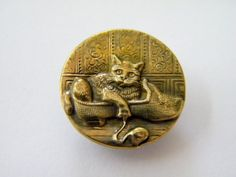 Antique Victorian metal /brass button featuring a cat in a shoe playing with a ball of yarn.