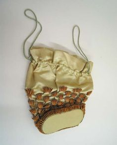 Date Made: 1930s  Description:  Purse; ivory silk drawstring decorated with seeds and silver beads. Greenish grey cord is inserted through a pocket sewn at top of purse and acts as a drawstring. Lower two thirds of purse is decorated with a lattice of seeds and silver beads. Purse has a solidly formed bottom.