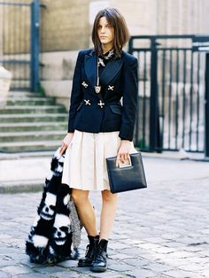 A fitted blazer is worn with a pleated skirt, combat boots, a fur coat, and a square handbag