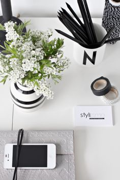 All black pens in white black lettered pencil container, flowers in white round vase, white business cards with black writing
