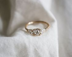Bespoke diamond engagement ring with reclaimed pear shape side diamonds in recycled yellow gold. #vintageengagementrings