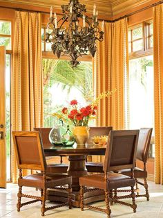 Elegant Color Scheme: Butterscotch + Chocolate  The sunny splendor of a Tuscan sunset inspired the decor in this lovely dining area. Although the space is elegantly appointed, the cozy color creates an inviting corner. Butterscotch-yellow draperies accented with red stripes convey an understated grace while providing an unencumbered view of the garden.