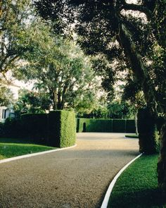 howard slatkin - driveway with box hedge. Nice hardscape treatment..either loos stone or tar and chip. Looks like it is edged with concrete, but also Belgian Block could have been used.