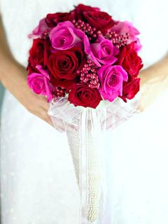Red and pink roses mix easily with pink berries with nary a leaf or green in sight. A pearl-covered cone and sheer ribbon bow give this type of bouquet a new look.