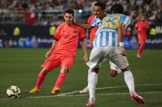 Lionel Messi of F.C. Barcelona is tackled by Weligton Robson of Malaga CF during the La Liga match between Malaga CF and FC Barcelona at La Rosaleda studium on September 24, 2014 in Malaga, Spain.