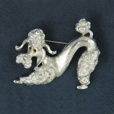 Monet Poodle Silvertone Brooch Pin. My 3rd grade teacher Mrs Scogland gave a pin like this to me in a sliver box with red velvet. I and 3 other little girls went to her house for tea! She live 2 blocks from me, by the creek. Her and her husband never had any children. She was one of the kindest teachers ever. I remember to be very old...I am now 54, I will never know how old she really was. I was a very lucky little girl. I now have a little blue mini poodle named Howie and I adore him!