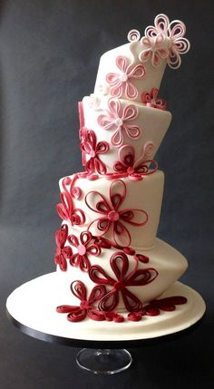 Lopsided red and pink wedding cake with floral design fun and quirky and sweet…