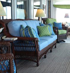 Dark brown wicker with blue cushions.