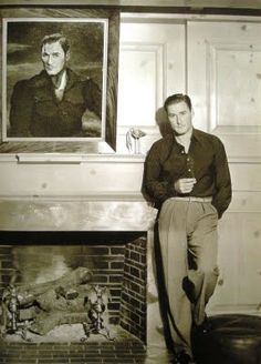 Errol Flynn posing in front of Decker portrait - his Mulholland Farm living room circa 1940's