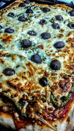 Coca de cebolla, pimientos verdes, queso azul, mozzarella, y aceitunas