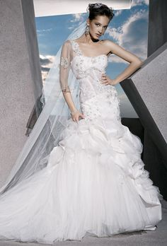 Brides: Demetrios - Sensualle. One-shoulder dress with a soft sweetheart neckline, lace-up back and corset bodice embellished with floral beading. Flared skirt features layers of taffeta bustles and tulle. Sample shown ivory/sheer. Available in Diamond white, white/sheer, ivory/sheer, & diamond white/sheer.