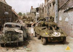 A unit of the US 25th Cavalry Reconnaissance Squadron (Mechanized), 4th Armored Division moves through the village of Le Repas near Villiers-Fossard, in Normandy on July 31, 1944. Up front are two M8...