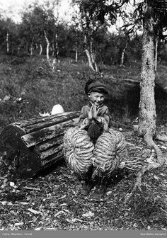 Gustav Skum, grand-son of the artist Nils Nilsson Skum, with bunches of sedge hay used for isolation in shoes. Girjas Sami community, Gällivare parish, Lapland, Sweden. 1936   Ernst Manker. Nordiska Museet.