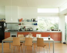 The orange-painted MDF cabinets add a pop of color to the sun-washed kitchen.  Photo by: Matthew Williams      Read more: http://www.dwell.com/slideshows/bach-to-the-beach.html?slide=17=y=true##ixzz25iLQsKQf