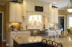 White Cabinets with New Venetian Gold Granite Counters and Exposed Brick Wall